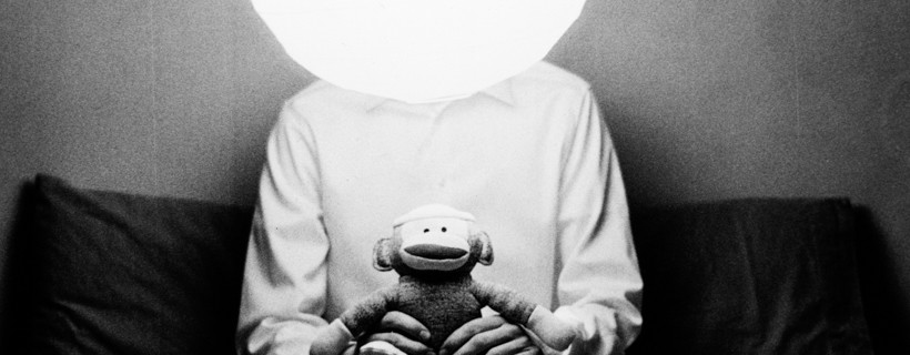 Black and white image of a figure with a orb of light for a head who is also holding a sock monkey in their hands