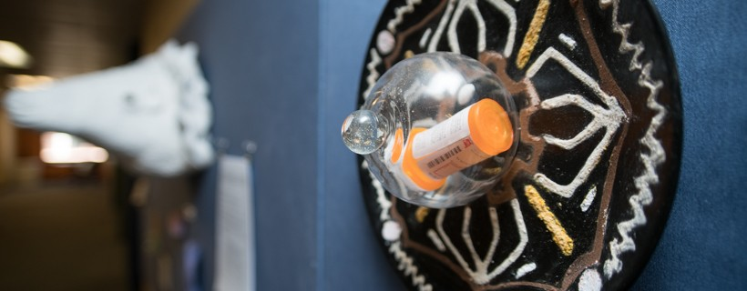 Sculpture with pill bottle encased in a glass orb on a circular plate