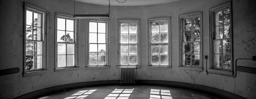 Black and white image of the interior of a circular room with windows