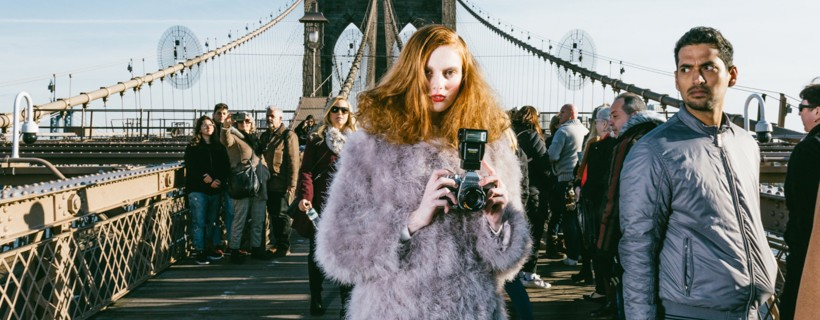 photograph of woman in fur coat holding camera standing on bridge