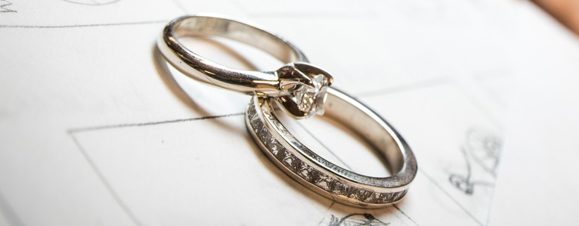 Wedding rings laid on design sketches