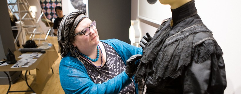 Person wearing black gloves assembles a black dress on a mannequin