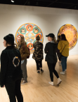 people gathered in gallery space in front of large, round circular paintings by faculty member Jay Constantine