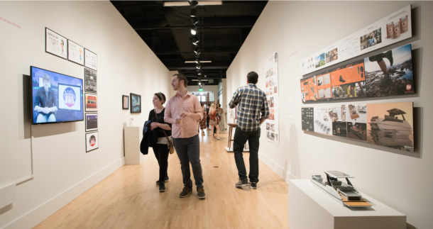 photograph of The Fed Galleries during Annual Excellence Awards 2018. People in gallery with digital display and print work.