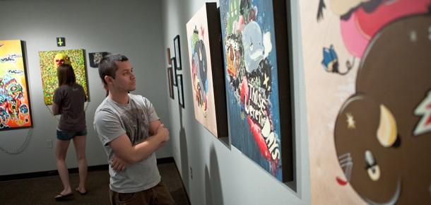 Gallery view of visitors and colorful illustration work in Trophy Room, Spring 2012
