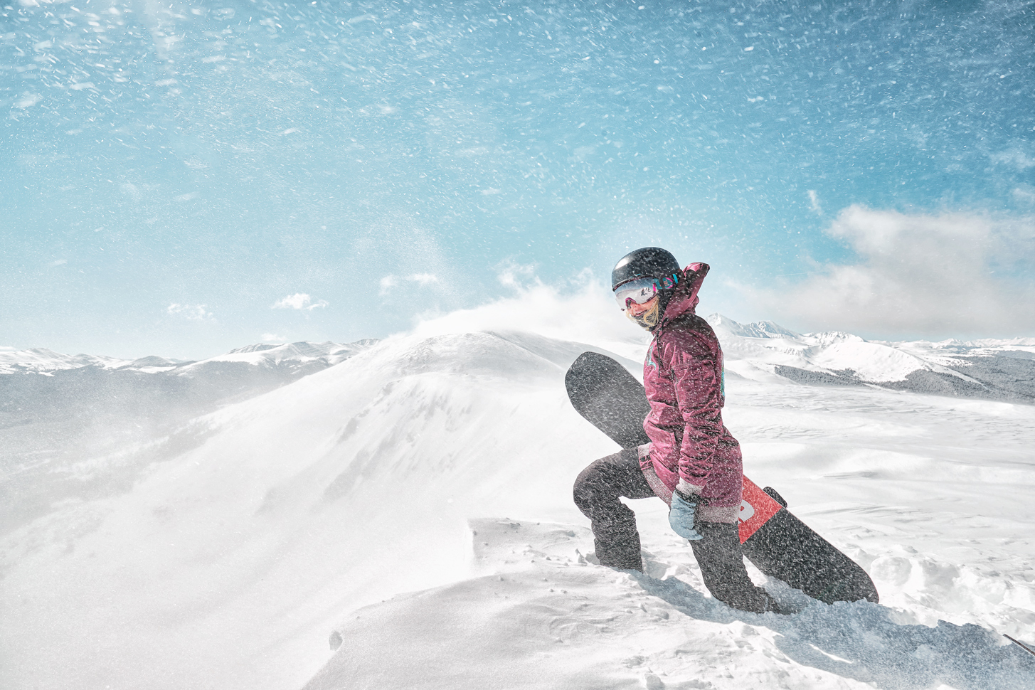 Woman snowboarder standing in a snow drift